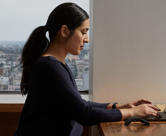 A person types on a Surface Laptop 3.