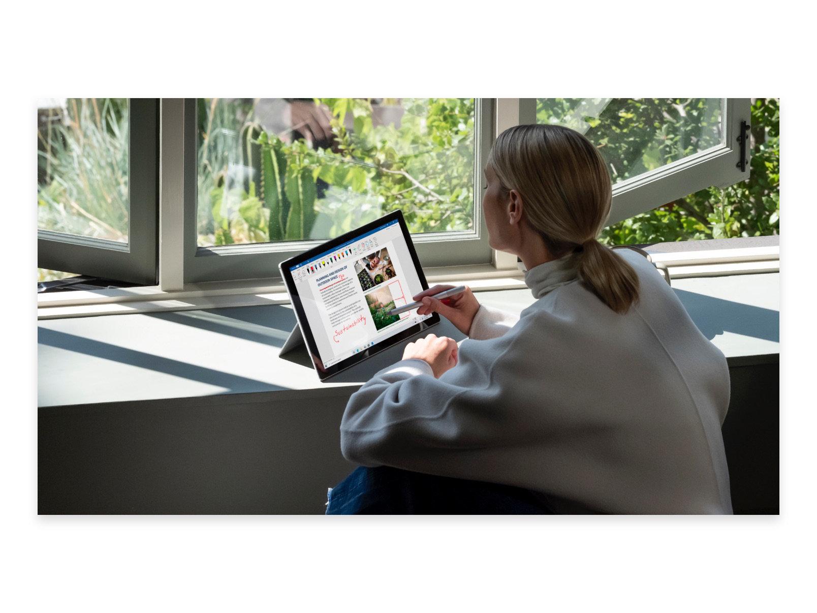 Personne assise devant une fenêtre et travaillant sur un document dans Word à l'aide d'un stylet et d'une tablette.