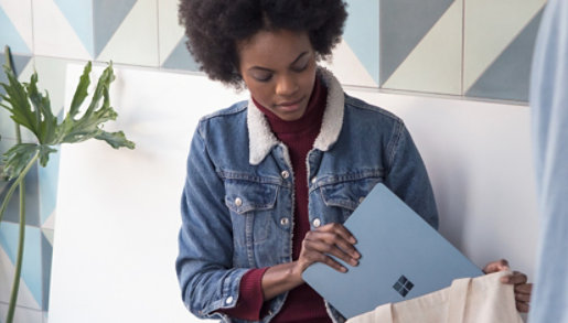 A woman puts a Surface device in her bag.