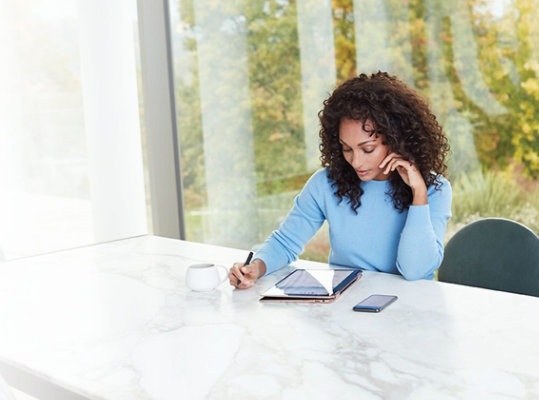 A woman uses a Windows 10 device while sitting at a table at home.