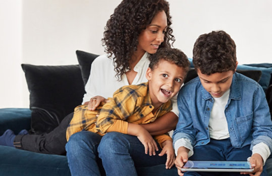 A woman on a couch with two children playing on a Windows 10 device.