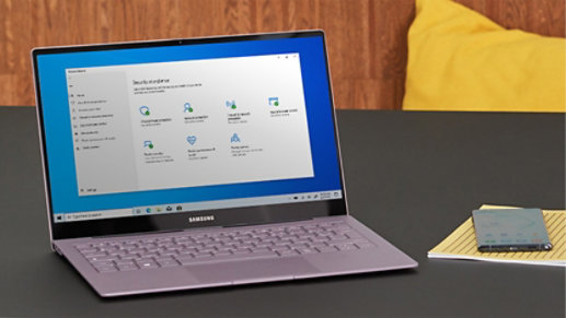 A laptop with a Security at a glance screen sits on a desk.