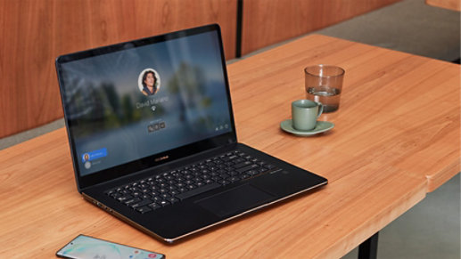 A laptop with a Windows Hello screen sits on a desk.