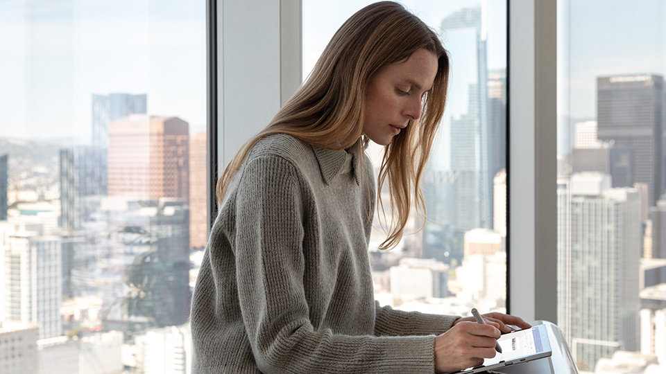 A person uses a Surface Pen and a Surface device.
