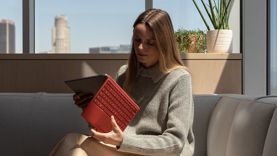 A person uses Surface Pro 7 with Type Cover while relaxing at home.