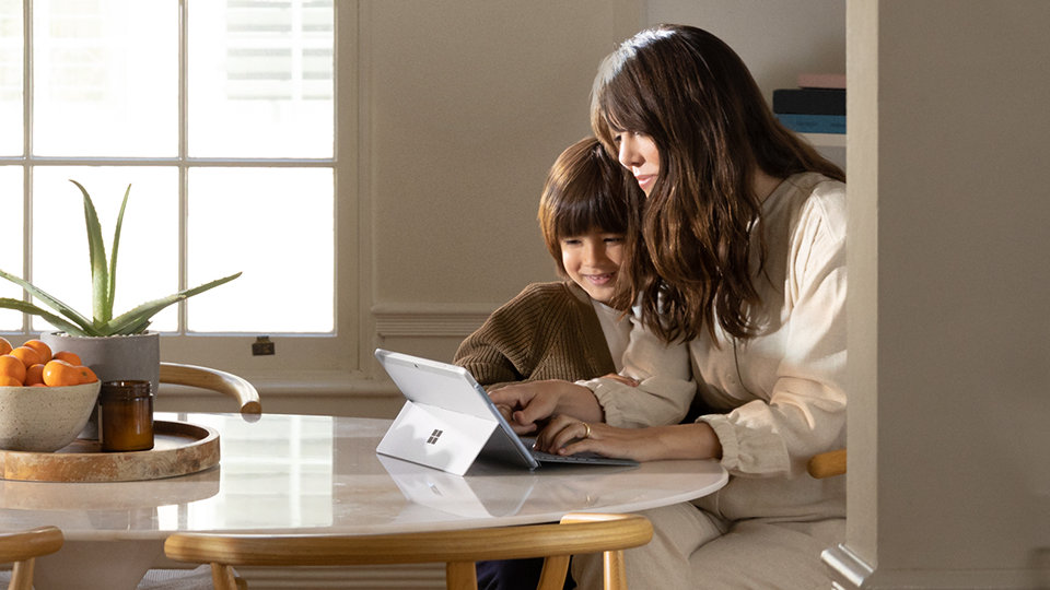 A woman and her child use the Surface Go with the type cover.