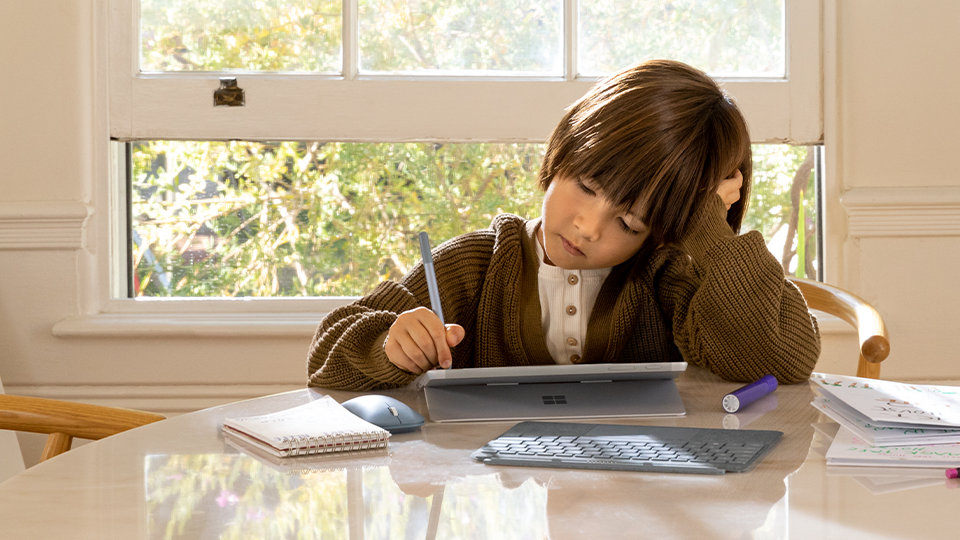 A child uses their Surface Go device at a table.