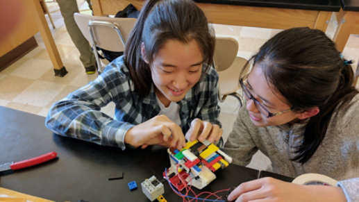 Two young girls work on a project together.
