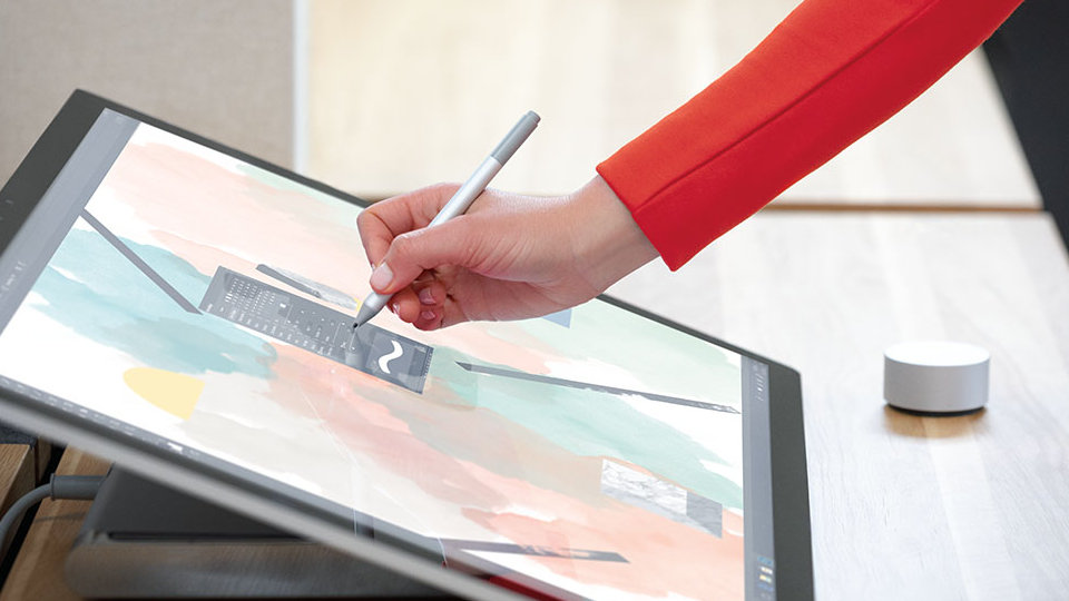A person writes on the screen of Surface Studio 2 in studio mode.