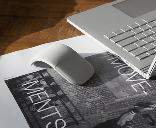 Surface Arc Mouse sits next to Surface device on a table.