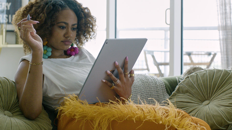 CreativeLive expert Reyna Noriega sitting on a couch, with a Surface Book 3 in one hand and Surface pen in the other