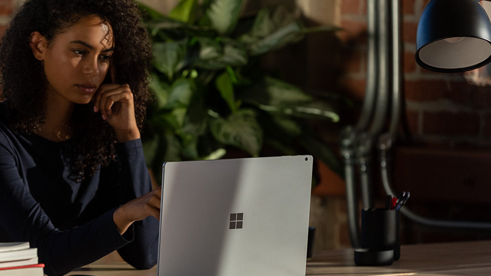 A woman uses Surface Book 3.