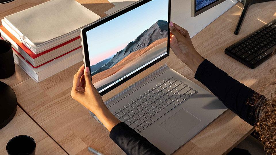 A woman is detaching the Surface Book 3 touchscreen.