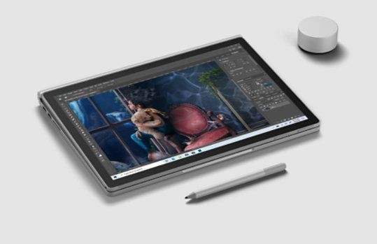 Surface Book 3 with Photoshop on screen, next to Surface Dial and Surface Pen.