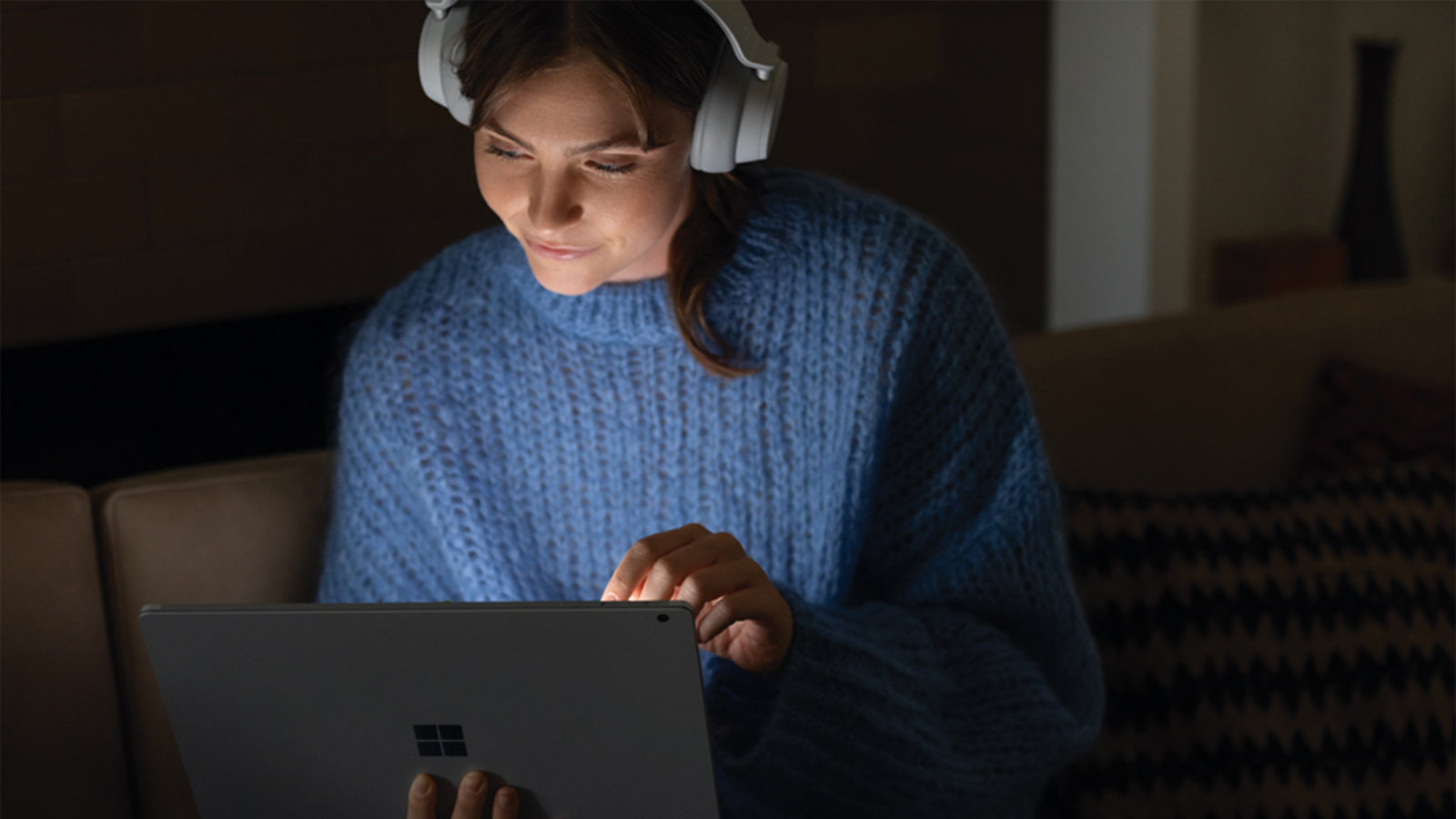 A woman listens to a movie with headphones.