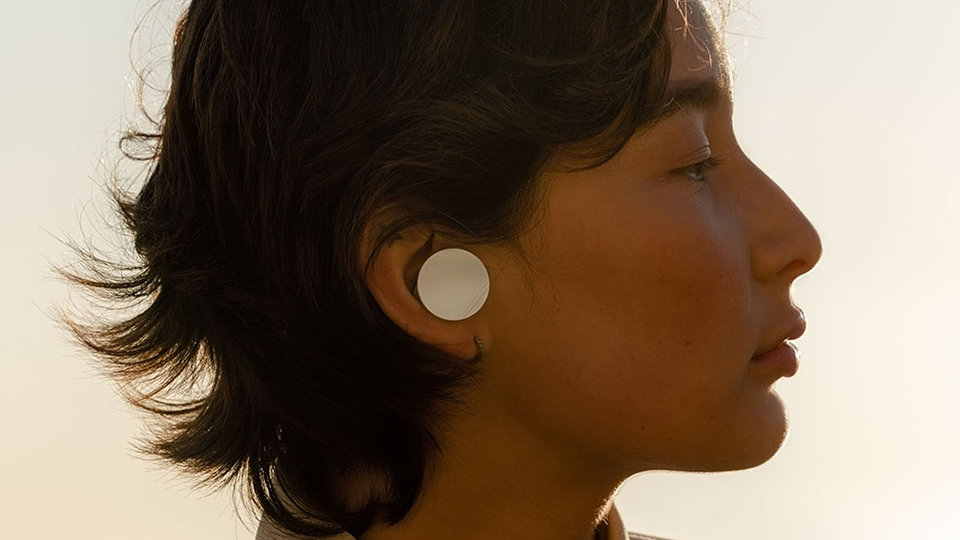 A woman uses Surface Earbuds to listen to emails.