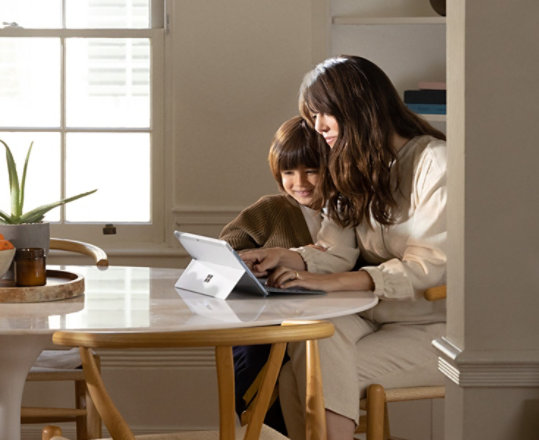 A mother and child using Surface Go 2.