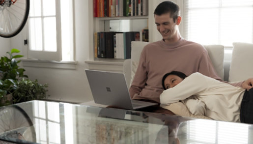 Two people watch videos on Surface Laptop 3 while relaxing at home.
