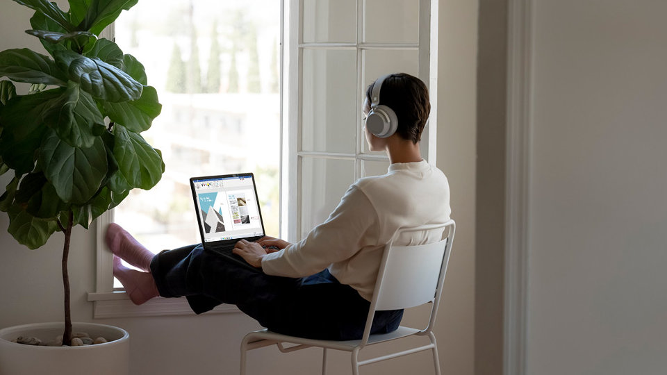 A person uses Surface Laptop 3 with headphones on.