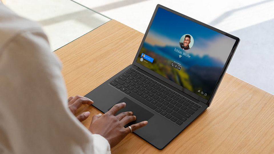 A person uses Windows Hello sign-in to unlock Surface Laptop 3.