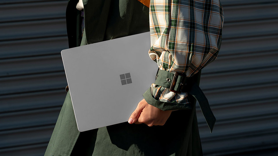 A person carries Surface Laptop 3 at their side.