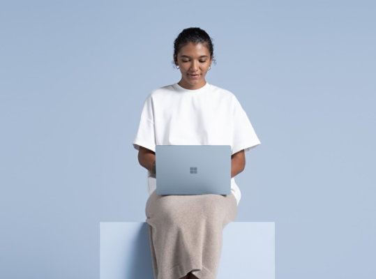 A person uses Surface Laptop 4 in Ice Blue.