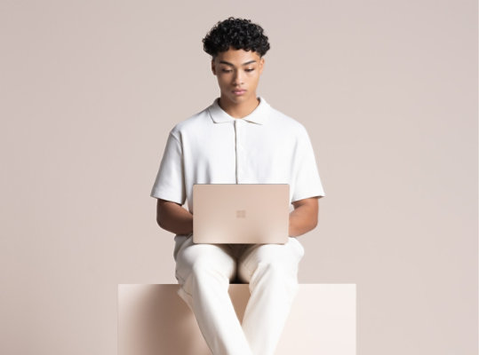 A person uses Surface Laptop 4 in Sandstone.