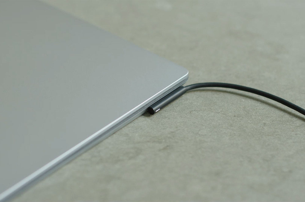 A Surface Laptop 4 with a charging cable.
