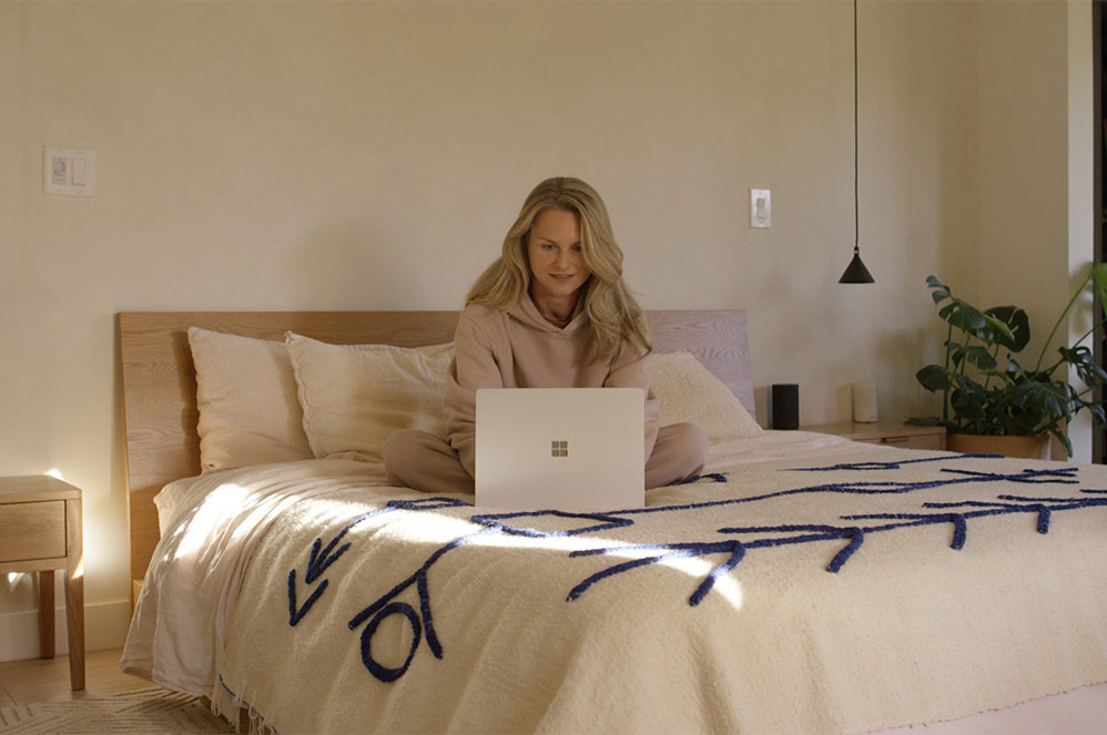 A person uses their Surface Laptop 4 while sitting in bed.