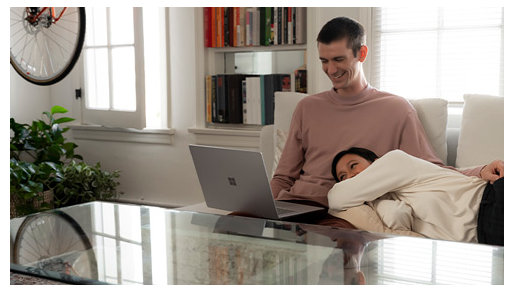 Two people relax on a couch while using the Surface Laptop 3.