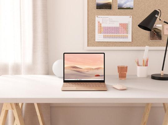 Sandstone Surface Laptop Go on a desk.