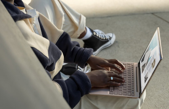 A person types on the full-size keyboard of Surface Laptop Go.
