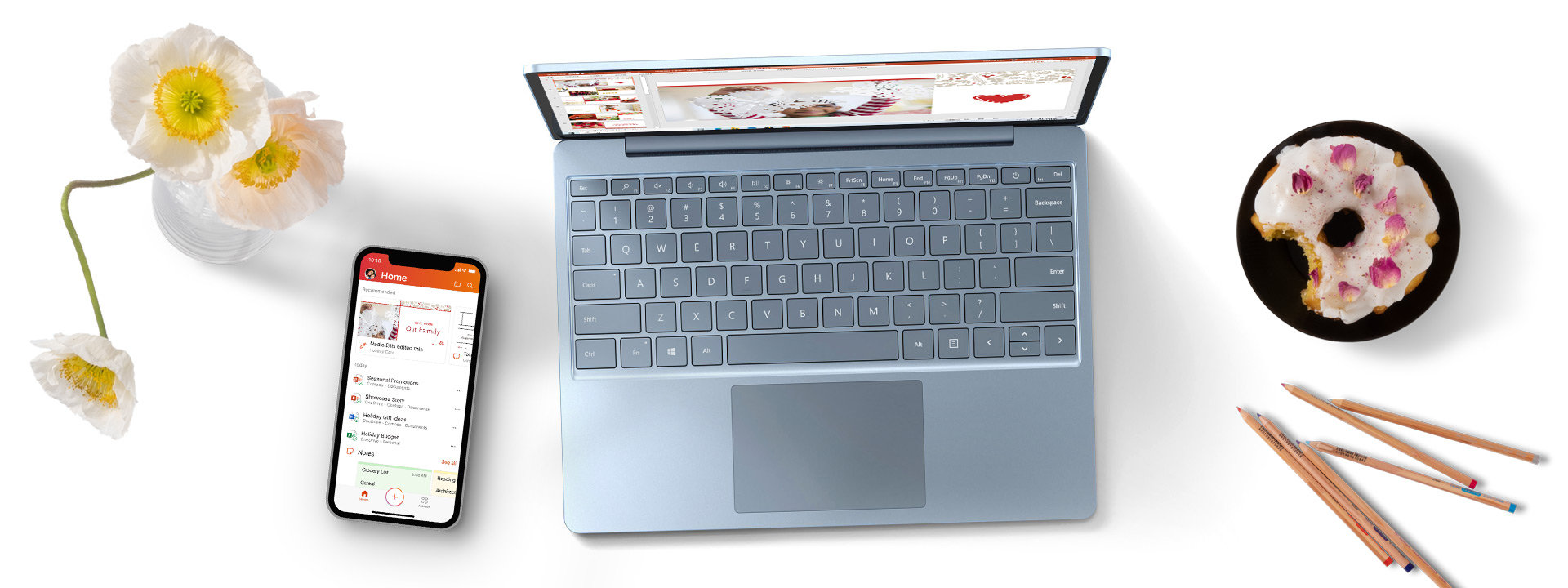 Surface Laptop Go with a phone, pencils, flower vase, and donut on a plate.