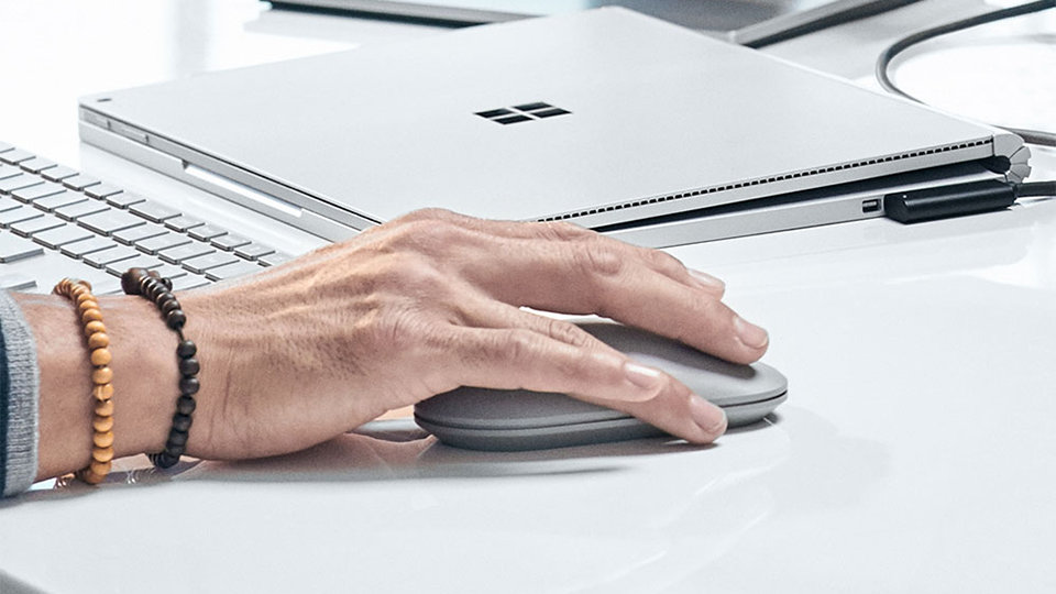 A person's hand upon the Surface Mouse.
