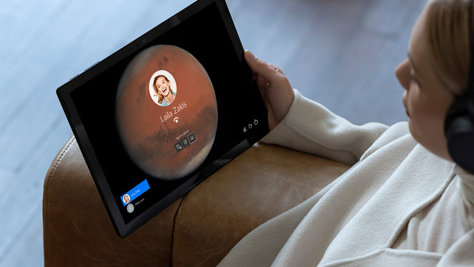 A person uses Windows Hello sign-in to unlock Surface Pro 7.