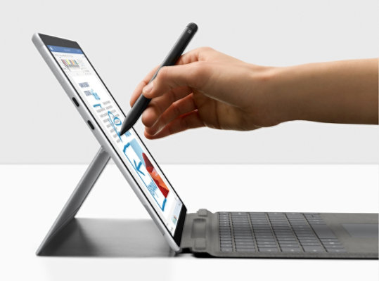 A person sketching on the screen of a Surface Pro X.