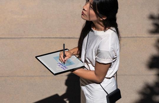 A woman writing on Surface Pro X.