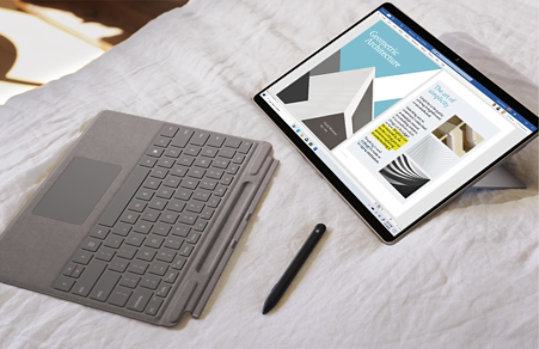 Surface Pro X with the Type Cover detached and Slim pen nearby.
