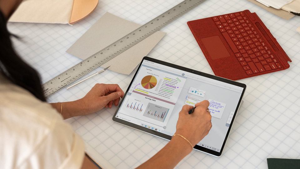 A person using a Surface Pro X with detached Type Cover nearby.