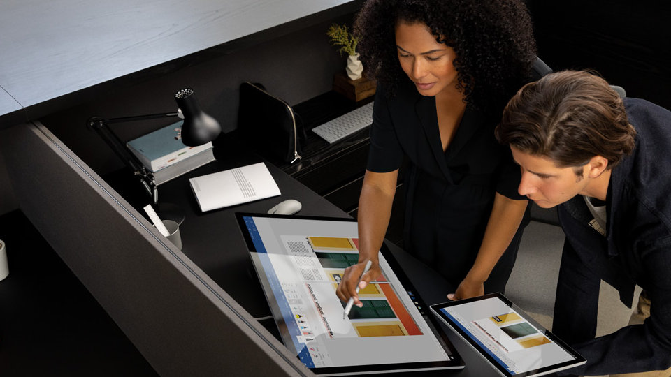 Two coworkers use Microsoft 365 apps on Surface Studio 2.