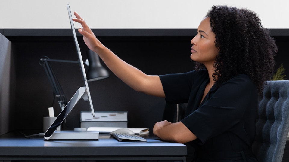 A person touches the display of Surface Studio 2 while sitting at a desk.