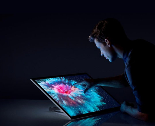 A person touches the display of Surface Studio 2.