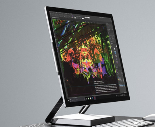 Surface Studio 2 on a desk with a keyboard and mouse.