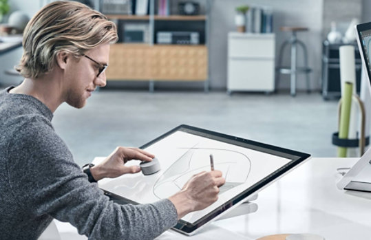 A man uses Surface Dial on the display of Surface Studio 2.