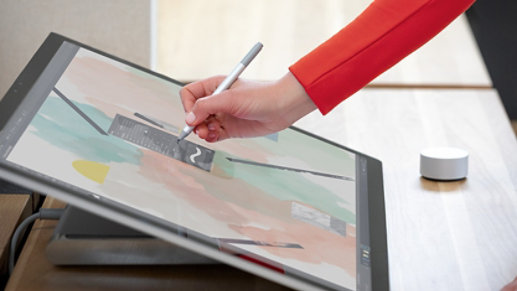 A person uses Surface Dial and Surface Pen with Surface Studio 2.