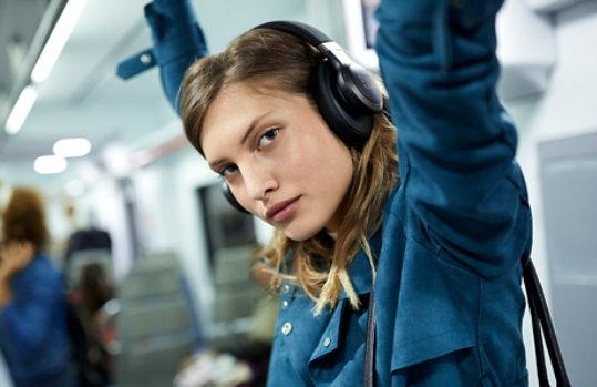 A woman wears JBL Headphones in a crowded subway.