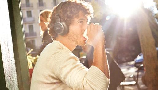 A man wears JBL Headphones in an outdoor cafe.