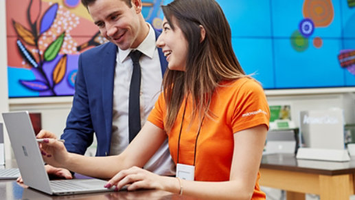 A Microsoft Store associate helps a customer set up a Surface device.