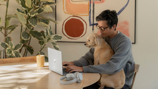 An adult male using Surface laptop 4 13 inch Platinum with dog on his lap