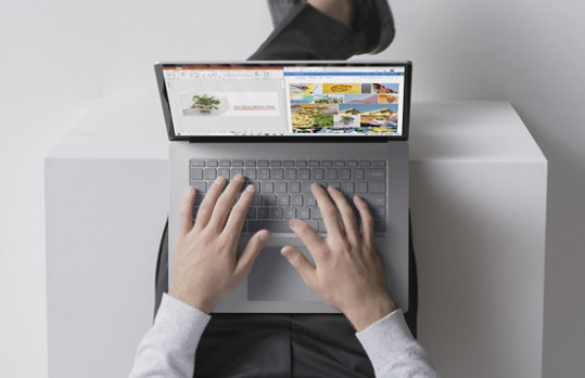 Surface Laptop 4 Platinum on desk with Excel, PowerPoint and OneNote snapped on screen